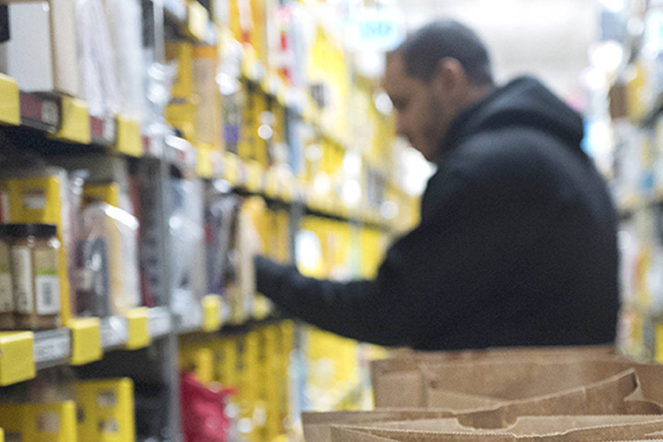 In this Dec. 20, 2017, photo, a clerk reaches to a shelf to pick an item for a customer order at the Amazon Prime warehouse, in New York. (AP Photo/Mark Lennihan, File)