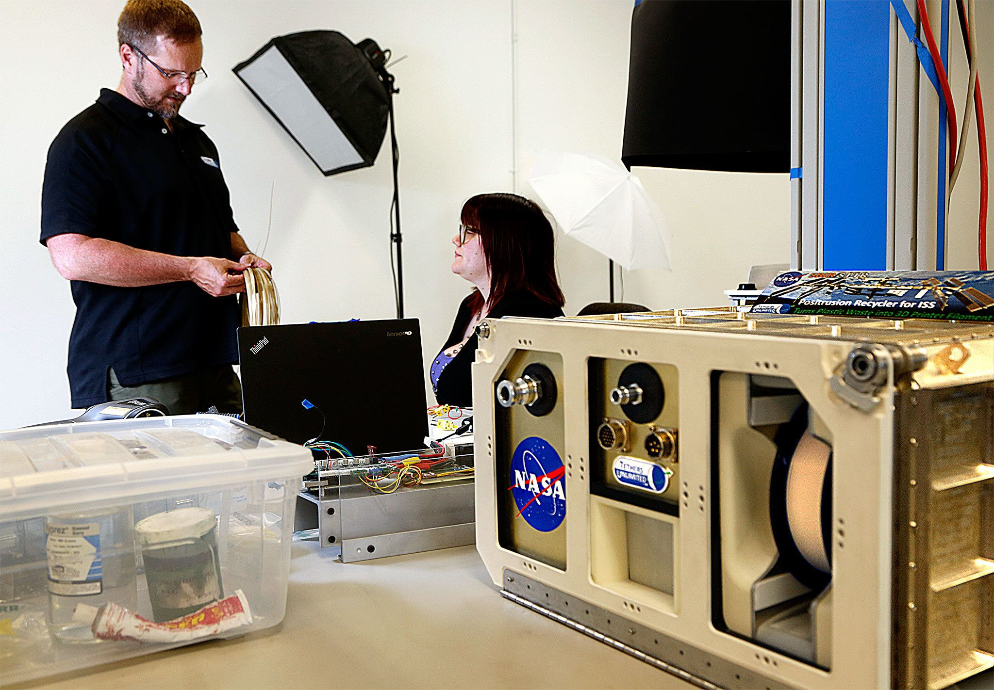 Dr. Robert Hoyt (left, holding a roll of the 3D printer filament) talks with Dr. Rachel Muhlbauer in an area of the lab where they have been photographing component parts of TUI's Positrusion Recycler for the International Space Station. The recycler turns plastic waste into 3D printer filament that can be used to create needed replacement parts for repairs conducted in space.