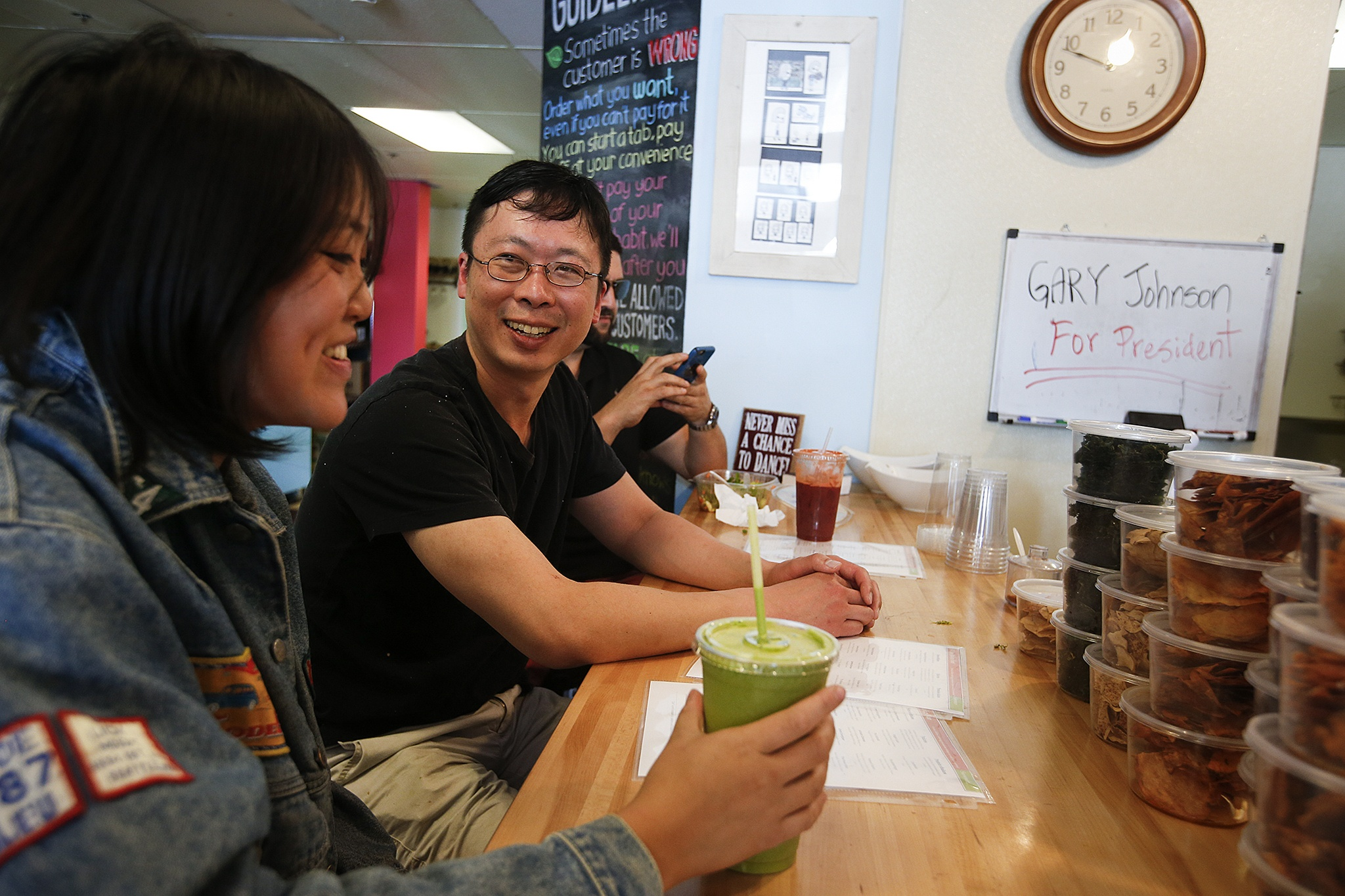 Alive Juice Bar owner Andrew Ho (center) chats with customers at his Ballinger Way store July 20. Ho asks that customers don't form lines, but rather say their order as soon as they decide. (Ian Terry / The Herald)