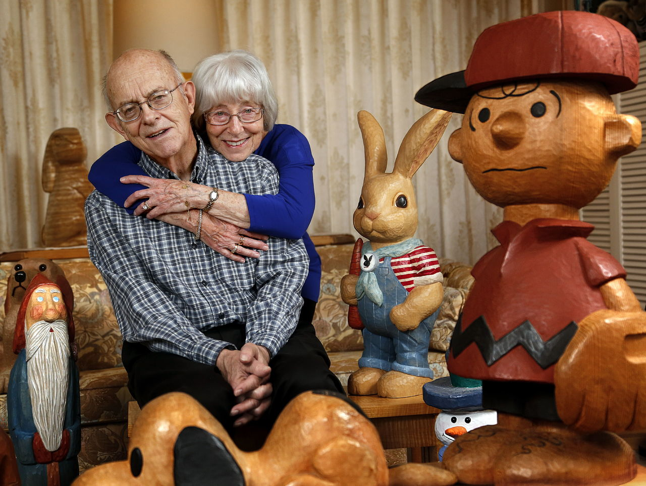 At home in Everett, Ed and Betty Morrow, both 81, enjoy the company of some of Ed's lifelike creations last week. The Morrows were honored by the Everett Museum of History for long-time community involvement, plus their efforts to establish a much-needed museum in Everett.