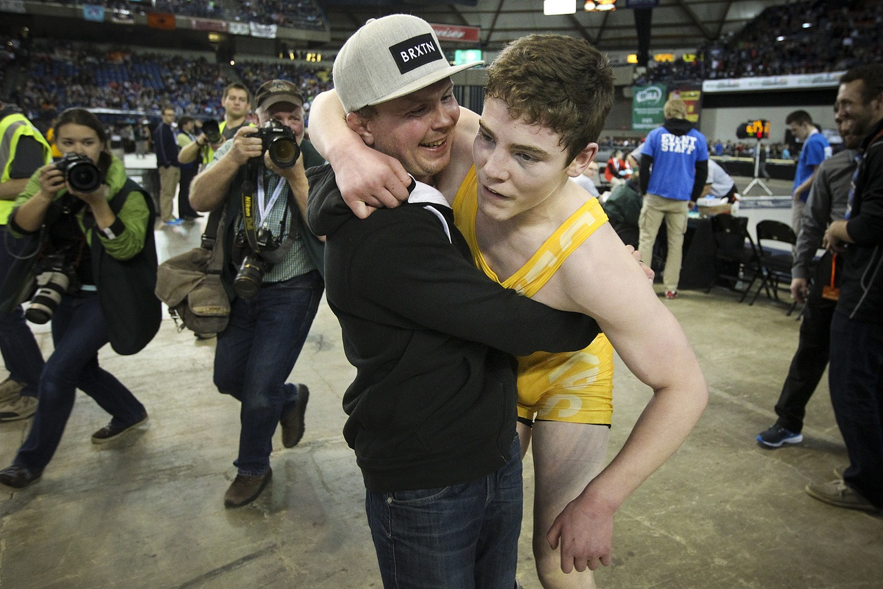Lake Stevens wrestling alum Burke Barnes congratulates the Vikings' Michael Soler (right) on his fourth state title during Mat Classic on Saturday.