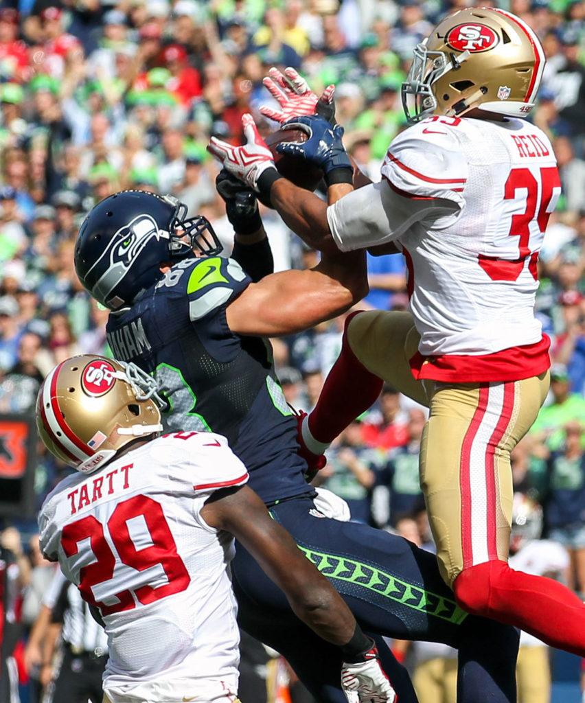 Seahawks tight end Jimmy Graham muscles in a reception with 49ers safety Jaquiski Tartt, left, and 49ers safety Eric Reid defending Sunday afternoon at Century Link Field in Seattle on September 25, 2016. The Seahawks are 2-1 after defeating the 49ers 37-18. (Kevin Clark / The Herald)