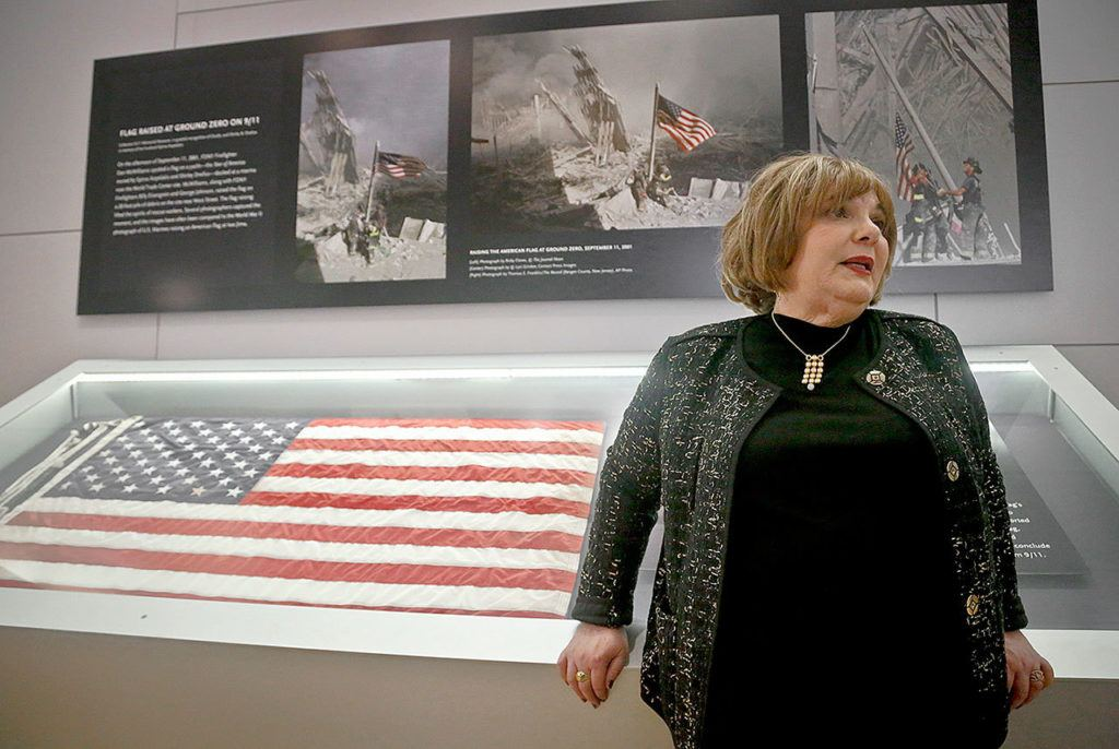 Shirley Dreifus, the original owner of the American flag, left, that firefighters hoisted at ground zero in the hours after the 9/11 terror attacks, speaks during an interview at the Sept. 11 museum Thursday in New York. After disappearing for more than a decade, the 3-foot-by-5-foot flag goes on display Thursday at the museum. (AP Photo/Bebeto Matthews)