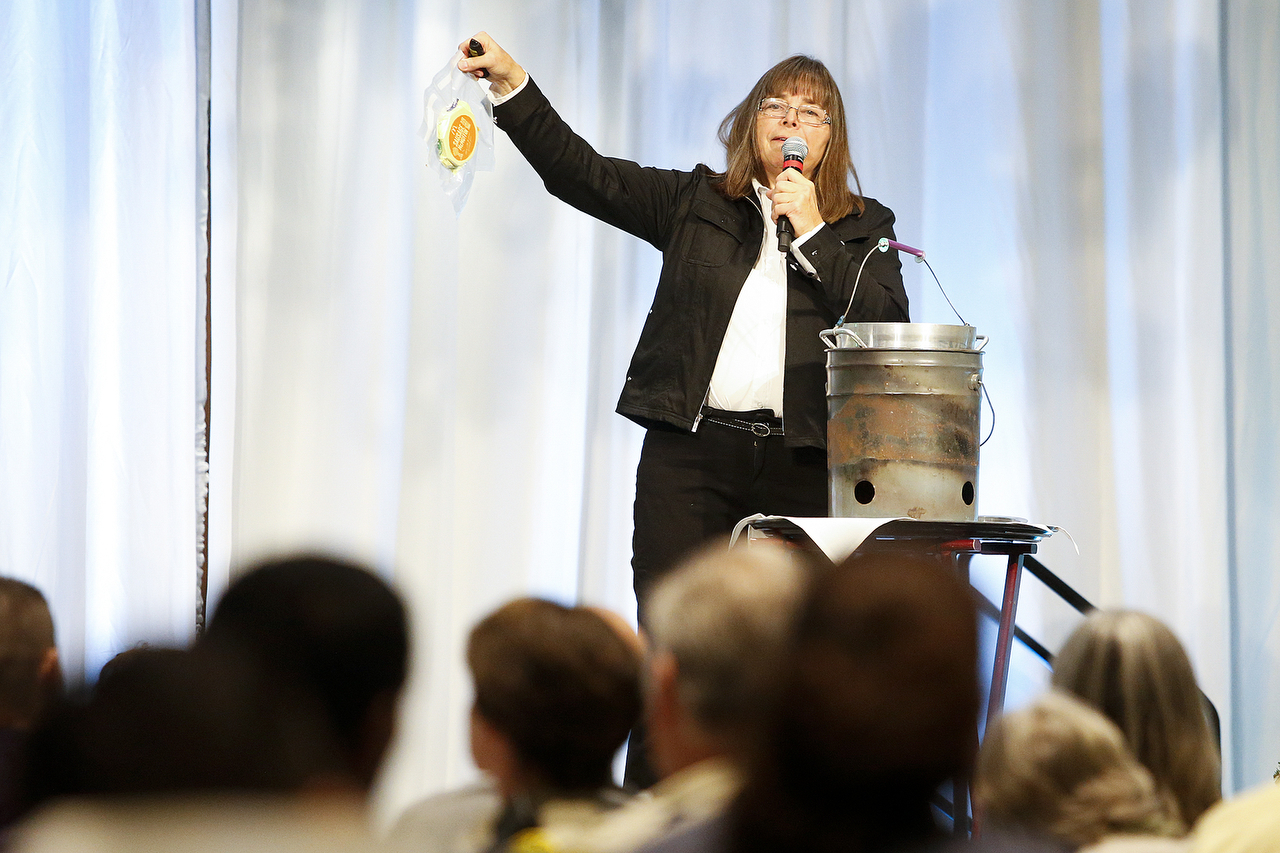 Jan Steves shows a crowd gathered for the Domestic Violence Services of Snohomish County what she eats along the trail when competing in the Iditarod sled dog race in Alaska during a luncheon for the organization at Xfinity Arena in Everett on Wednesday. (Ian Terry / The Herald)