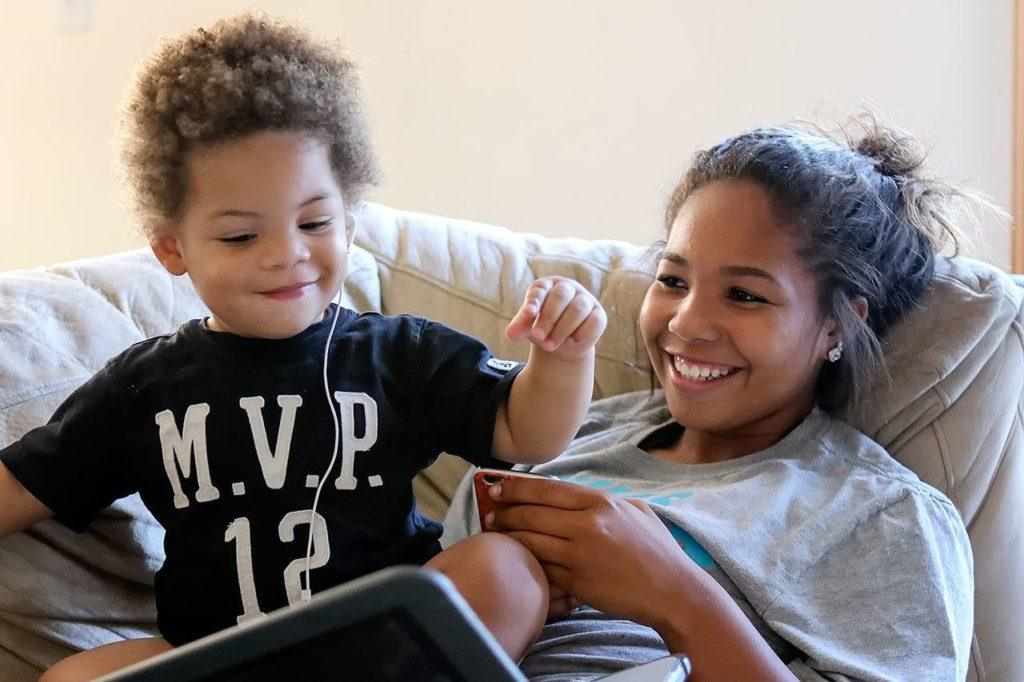 "DeJohn Ward-Taylor, ""Little DJ,"" bops to music in the lap of his aunt, Veronika Taylor, at their home in Marysville. Little DJ lost his father to suicide four months before he was born. (Kevin Clark / The Herald)"