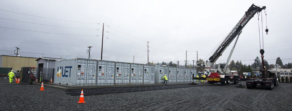 A crane sits next to a row of vanadium flow batteries at the PUD's Everett Substation. (Ian Terry / The Herald)