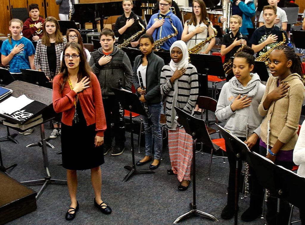 North Middle School band and choir director, Emily Cheever leads her class saluting the flag at the start of the day, June 15. (Dan Bates / The Herald)