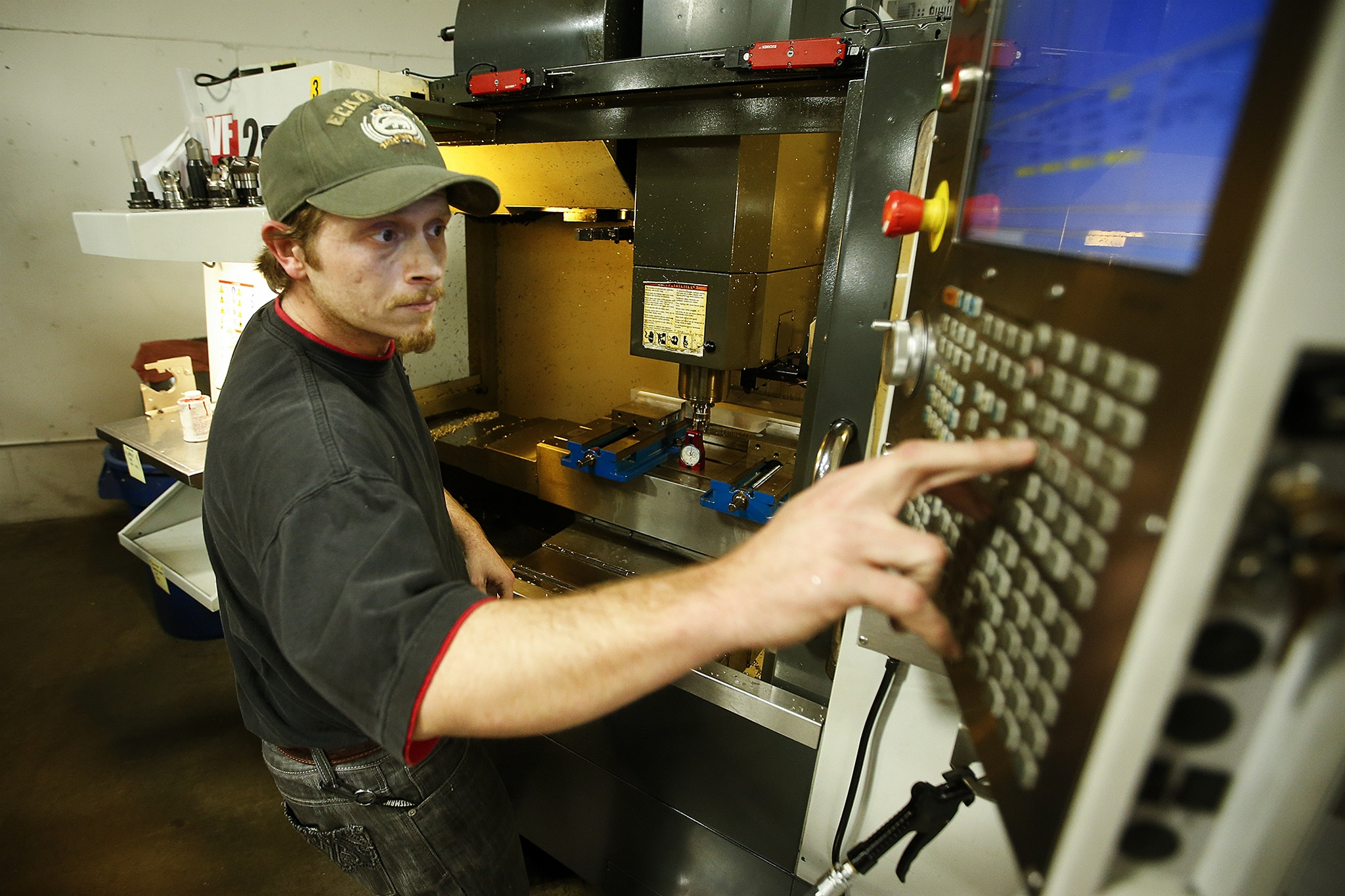 Machinist David Willis makes adjustments to a CNC machine at RB Enterprises in Mukilteo on Wednesday. (Ian Terry / The Herald)