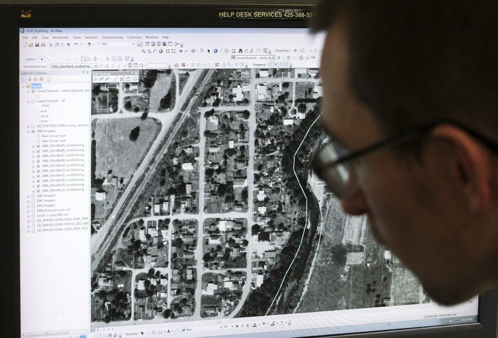 Joe Godfrey works on a computer-mapping project of a section of the Pilchuck River near Snohomish. (Ian Terry / The Herald)