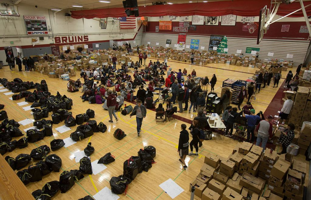 A gym full of students, alumni and volunteers gather and deliver food from Cascade High School on Wednesday, Dec. 14, 2016 in Everett, Wa. (Andy Bronson / The Herald)