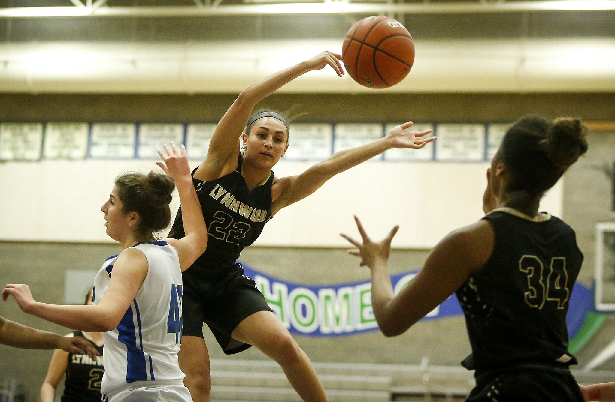 Lynnwood's Kaprice Boston (center) dishes the ball off to teammate Kia Crawford as Shorewood's Taryn Shelley (left) defends during a game at Shorewood High School in Shoreline on Friday. (Ian Terry / The Herald)
