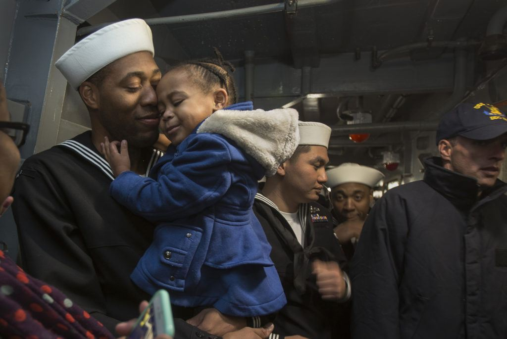 As his fellow crew heads to the mess hall to meet their families, Seaman Sean Tender and daughter Sydney, 2, hold each other after the USS Kidd docks at Everett Naval Station on Monday, Nov. 21, 2016 in Everett. (Andy Bronson / The Herald)