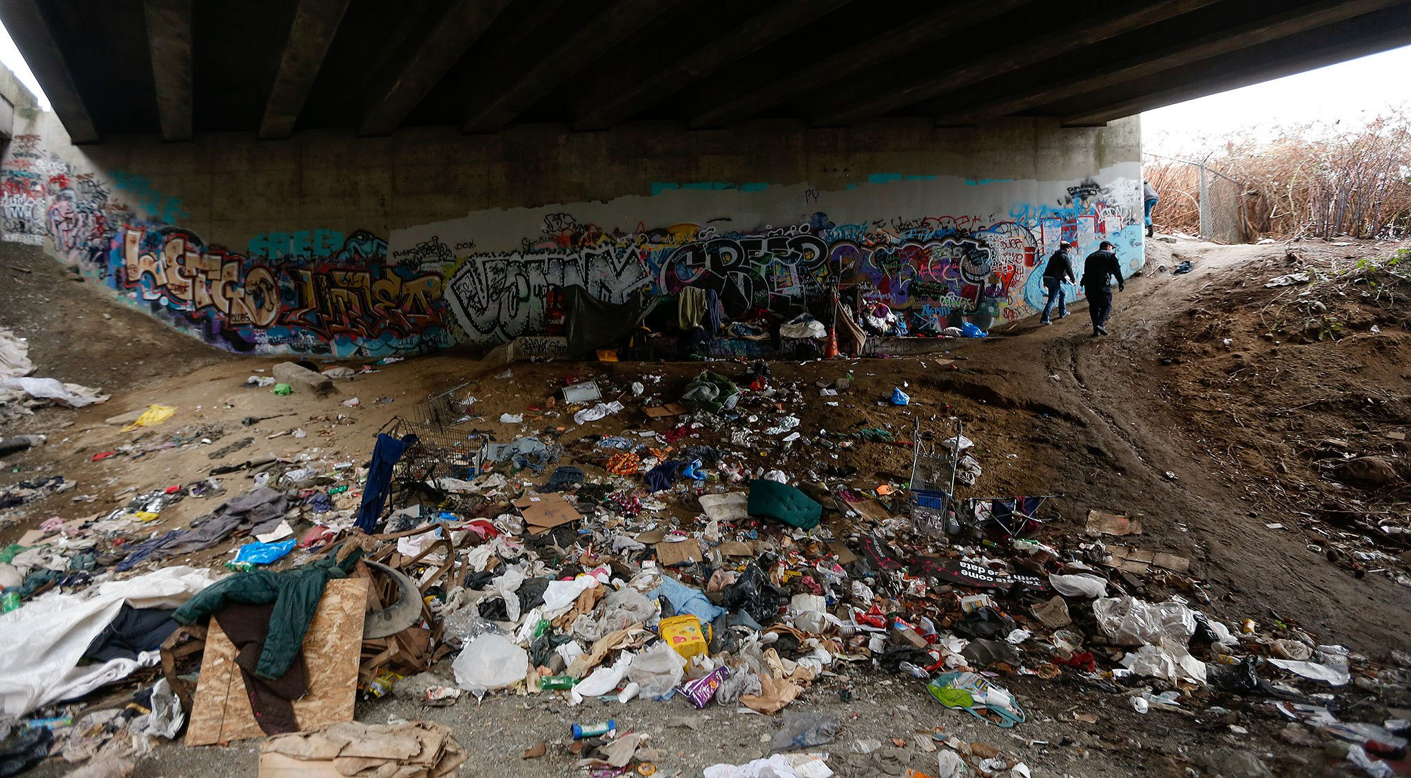 Police and social service workers search under an Everett overpass while administering a Point in Time survey of the homeless in Everett. The city of Everett is considering a lawsuit against Purdue Pharma, arguing the manufacturer of OxyContin is responsible for the community's surge in overdose deaths, homelessness and street crime. (Herald file)