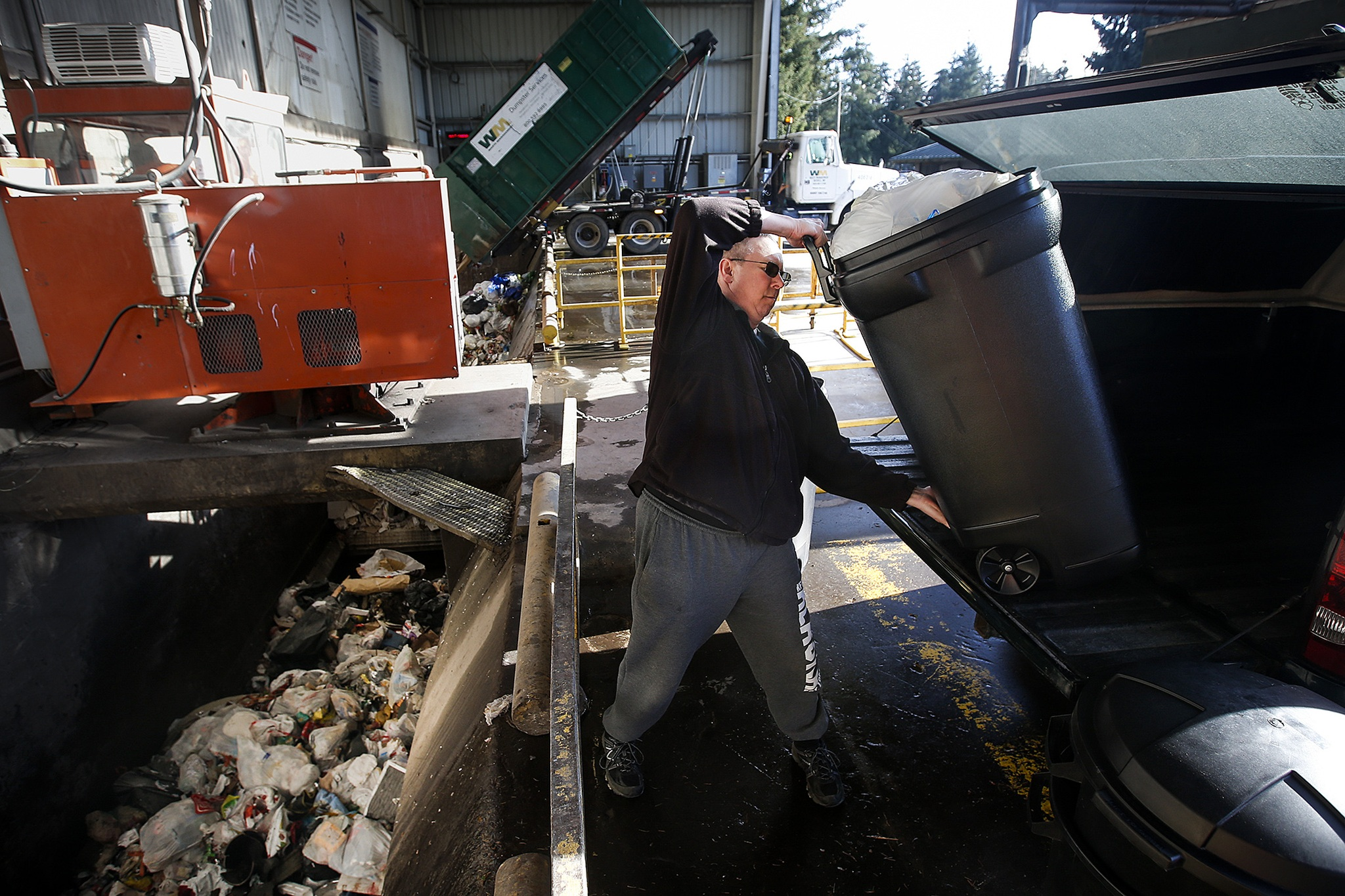 Scott Reed, of Stanwood, hoists a container of garbage out of his truck at the North County Transfer Station in Arlington on Thursday. The station collects, processes and offloads approximately 335 tons of waste each day. (Ian Terry / The Herald)