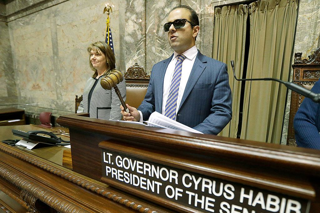 Washington Lt. Gov.-elect Cyrus Habib holds the gavel as he stands at the Senate chamber dais next to Senate Counsel Jeannie Gorrell on Thursday during a practice session to test technical equipment in Olympia. Habib, who will preside over the Senate, will be Washington's first blind lieutenant governor, and the Senate has undergone a makeover that incorporates Braille into that chamber's floor sessions that will allow Habib to know by the touch of his finger which lawmaker is seeking to be recognized to speak. (AP Photo/Ted S. Warren)