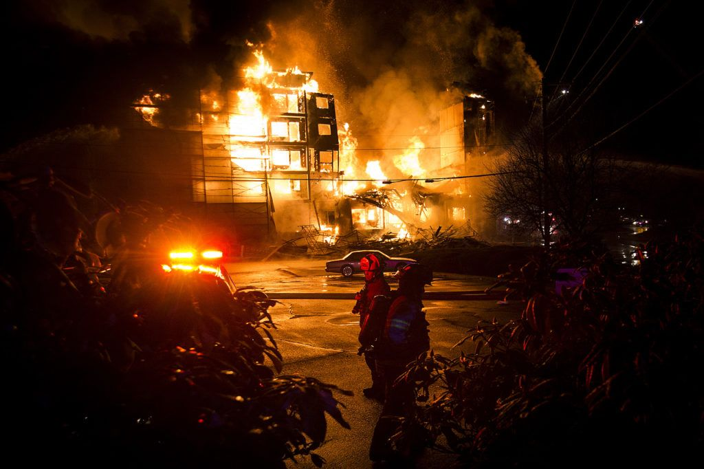 Firefighters prepare to bring in a water hose while an apartment complex under construction burns on Wednesday night on Scriber Lake Road in Lynnwood. (Ian Terry / The Herald)