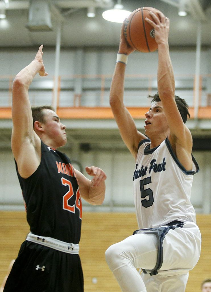 Glacier Peak's Justin Purcell (right) goes up for a shot as Monroe's Justin Folz defends during the Class 4A District 1 boys basketball championship game at Everett Community College on Thursday, Feb. 16. (Ian Terry / The Herald)