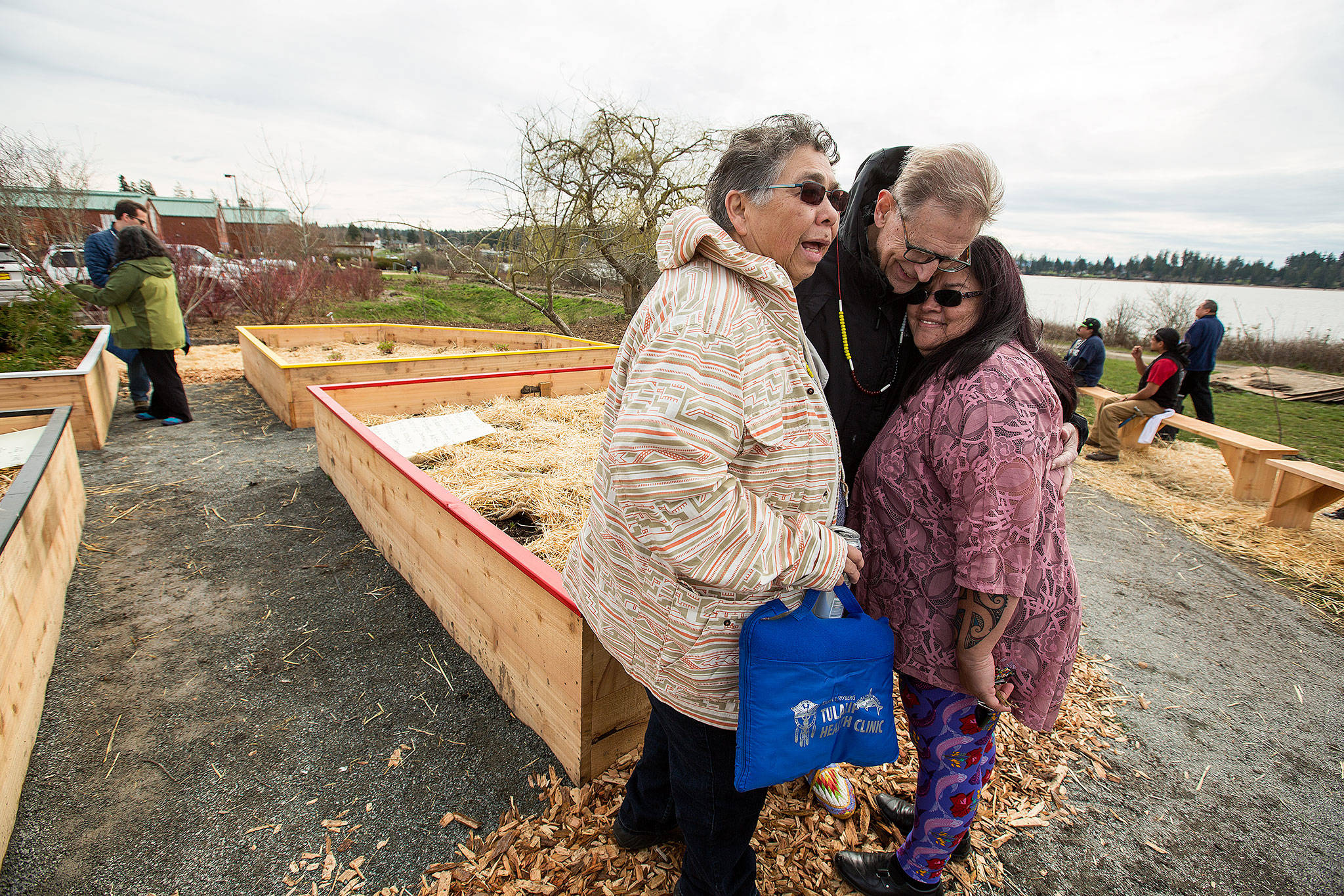 Father Pat Twohy is hugged by Tulalip Tribes Annette Napeahi (left) and Sheryl Fryberg after the dedication of a medicine wheel garden at the Tulalip Health Clinic on Monday, March 20. (Andy Bronson / The Herald)