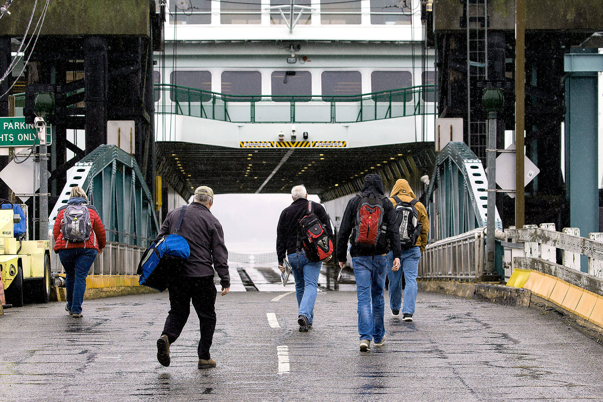 Pedestrians walk onto the Washington ferry Tokitae after cars are loaded for the Mukilteo to Clinton route on Monday. An overhead loading for pedestrians will be included in the city's new $134.7 million ferry terminal. (Andy Bronson / The Herald)