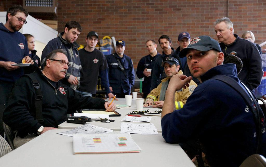 Oso fire Lt. Tim Harper, front right, and other first responders gather inside the fire station on March 22, 2014, in the hours after the mudslide. Harper, now a captain with the department, has help distribute over $500,000 in financial aid to victims and their families. (Annie Mulligan / The Herald)