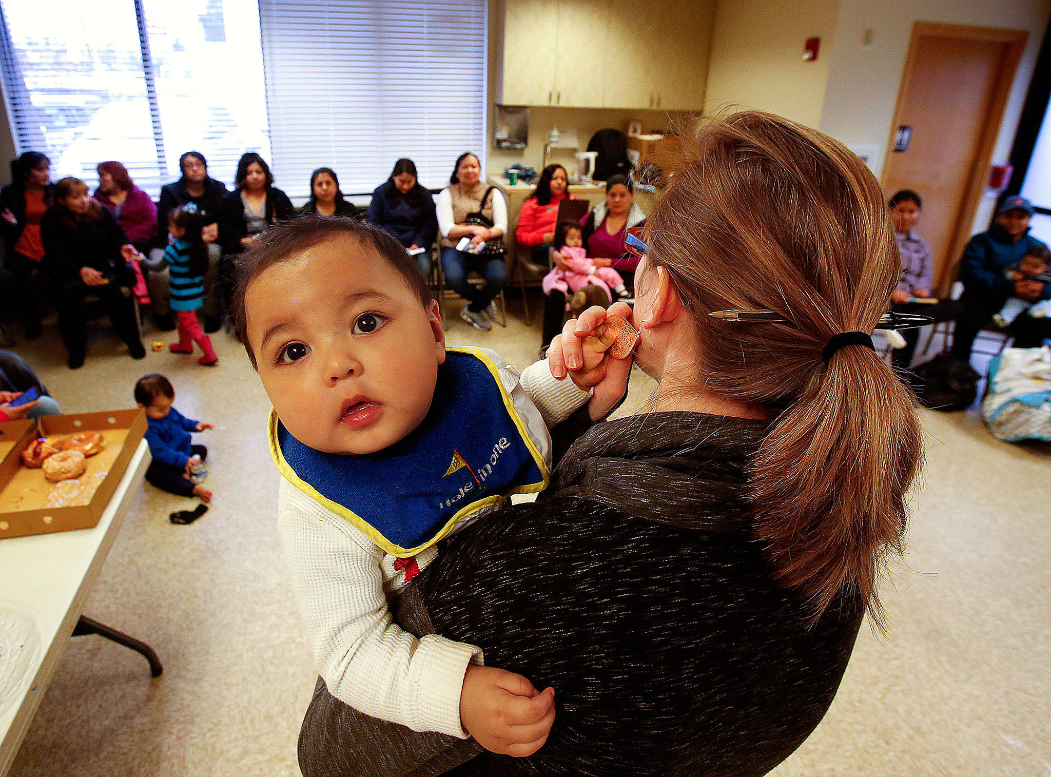 """While helping provide needed information for Casino Road-area moms at Hand in Hand, Angela Edwards walks around holding 7-month old Mario Gutierrez, who in turn holds her by the ear ring. """"He's my favorite little squishy baby,"""" says Edwards. (Dan Bates / The Herald)"""