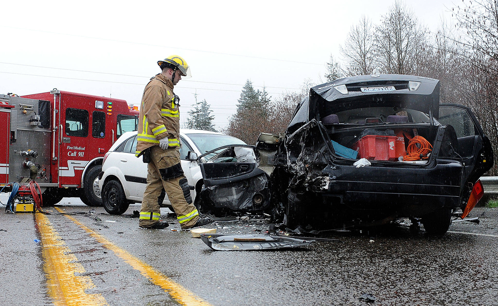 A firefighter looks over the aftermath of a head-on crash March 18 on U.S. 2, near Bickford Avenue, that cost a woman her life. The state is considering installing concrete median barriers on the highway between Bickford and the Pilchuck River. This crash happened near that stretch. (Doug Ramsay/ For The Herald)