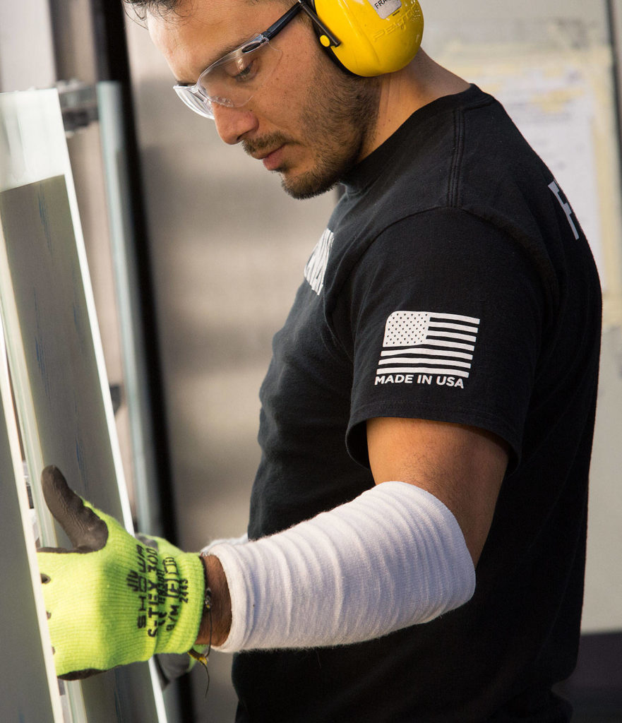 """An employee at Electric Mirror sports a shirt with a """"Made in the USA"""" logo on it as he works on mirrors Monday in Everett. (Andy Bronson / The Herald)"""