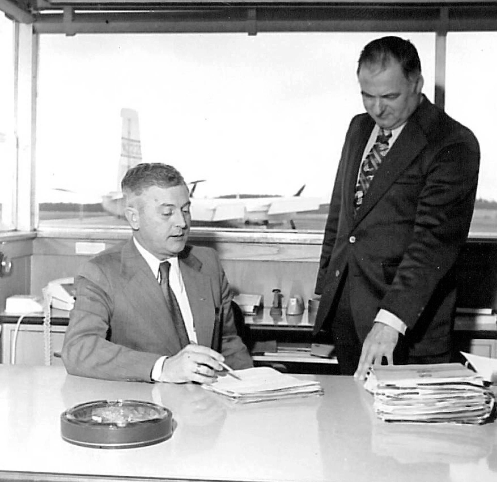 """Airport director George Petrie (left)and Don Bakken, a member of the Snohomish County Airport Commission, at Paine Field. Robert Best, Everett Herald publisher, and Petrie pitched the airport to Boeing president Bill Allen, who interrupted them. """"He said they had already optioned about 700 acres. Bob and I looked at each other in amazement,"""" Petrie told the Herald. """"He had no idea Boeing was thinking that big."""""""