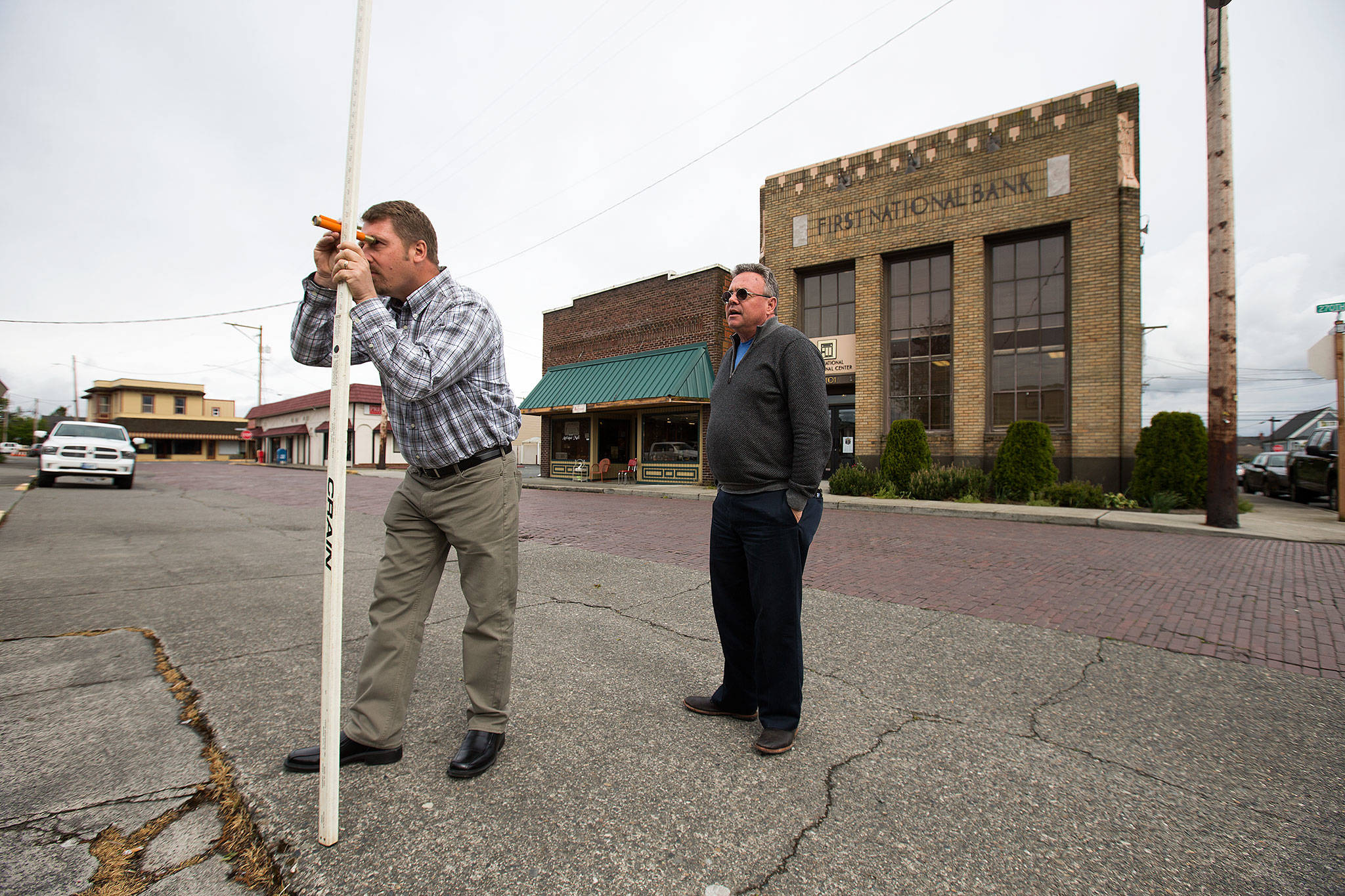 Landscape Architecture's Scott Lankford teaches Lee Ohlde how to shoot elevation measurements along 270th St. NW, one of many areas of Stanwood that lie in the flood zone, on Monday, May 15, 2017 in Stanwood, Wa. (Andy Bronson / The Herald)