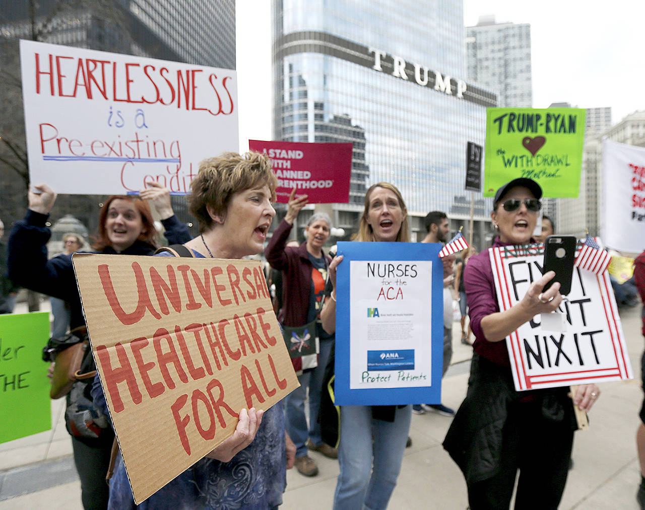 In March 24 photo, protesters gather across the Chicago River from Trump Tower to rally against the repeal of the Affordable Care Act, in Chicago. (AP Photo/Charles Rex Arbogast, File)