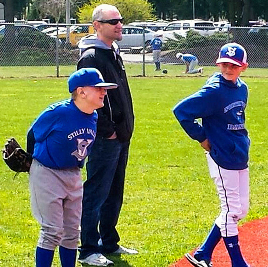 Jacob is all smiles as he plays second base. He is helped by his father, Steve Irish, and brother Noah. (Melanie Irish photo)