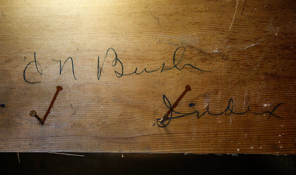 Blair Corson found the signature of Clarence Bush, the original owner of Bush House, when he removed a covering on the lower underside of a hotel staircase. (Dan Bates / The Herald)