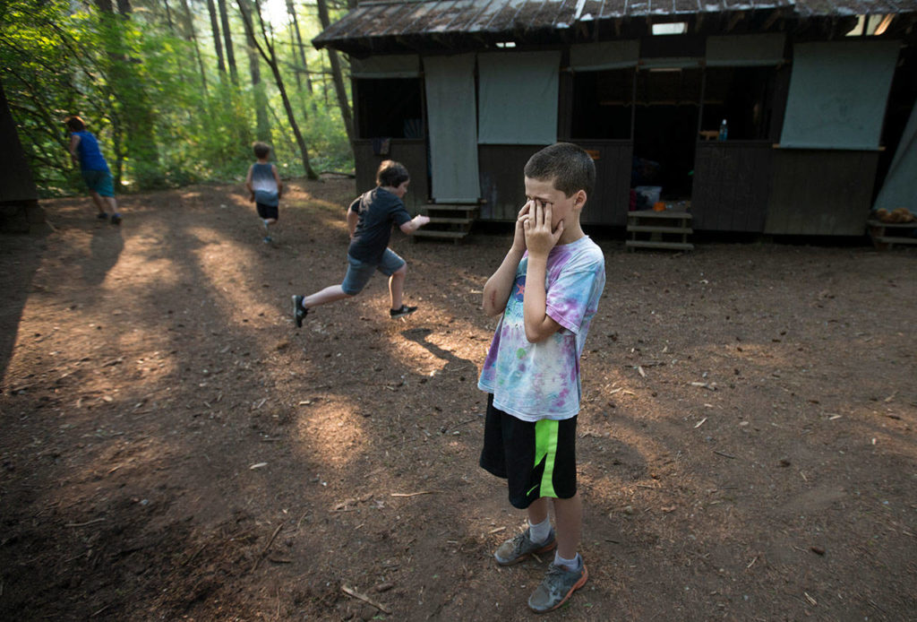 """Eli Zerba, 11, of Seattle, counts off as fellow campers hide during a game called """"Thicket"""" at Camp Killoqua on Monday in Stanwood. The game is similar to """"Hide-and-Seek,"""" but the counter never moves and players must be somewhat visible to the counter. (Andy Bronson / The Herald)"""