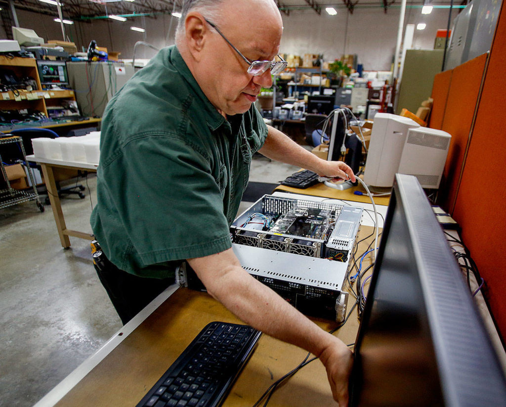 Teo Technologies electronic technician Dave Wright works on a server at the company's spacious manufacturing facility in Mukilteo. (Dan Bates / The Herald)