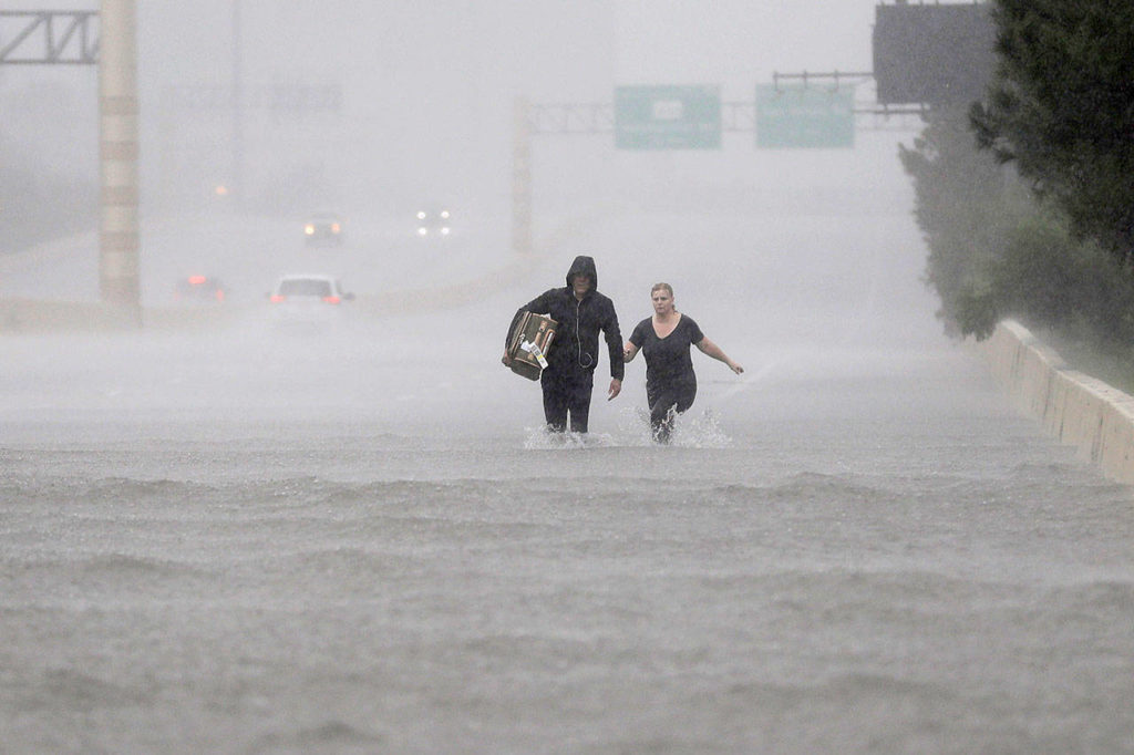 Two people walk down a flooded section of Interstate 610 in floodwaters from Tropical Storm Harvey on Sunday in Houston, Texas. (David J. Phillip / Associated Press)