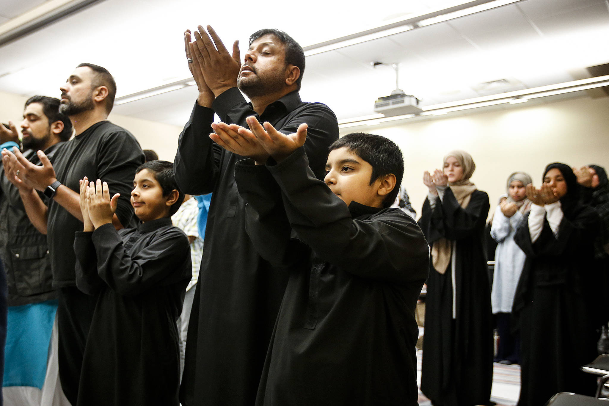 Ghulam Abbas (center) prays with his two sons Ammar (left), 8, and Ayaan, 8, during an evening service for the Zainab Center at the Lynnwood Convention Center on Thursday, Aug. 31. The center, which serves Shiite Muslims, is temporarily using the convention center's facilities while they await permits to begin repairing their water-damaged building in Lynnwood. (Ian Terry / The Herald)