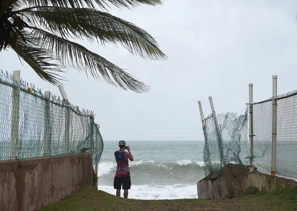 A man photographs the ocean before the arrival of Hurricane Irma in luquillo, Puerto Rico, on Wednesday. Irma roared into the Caribbean with record force early Wednesday, its 185-mph winds shaking homes and flooding buildings on a chain of small islands along a path toward Puerto Rico, Cuba and Hispaniola and a possible direct hit on densely populated South Florida. (AP Photo/Carlos Giusti)
