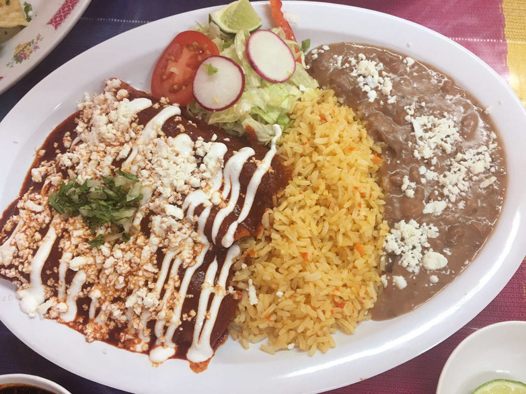 Chicken enchiladas with red sauce, cheese and crema, plus rice and beans makes for a seriously filling dish at Ade's Mexican Deli. (Ben Watanabe / The Herald)