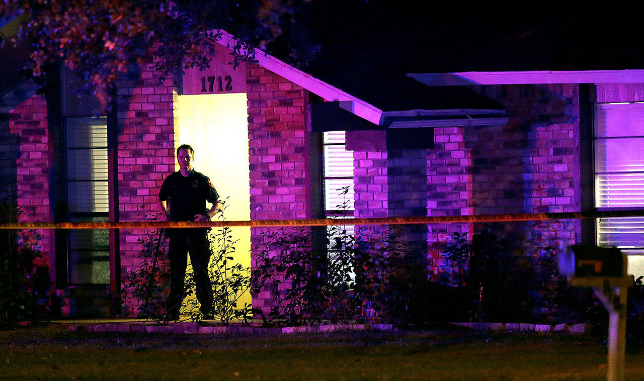 A police officer stands guard outside the scene of a mass shooting in Plano, Texas, Sunday. (AP Photo/LM Otero)