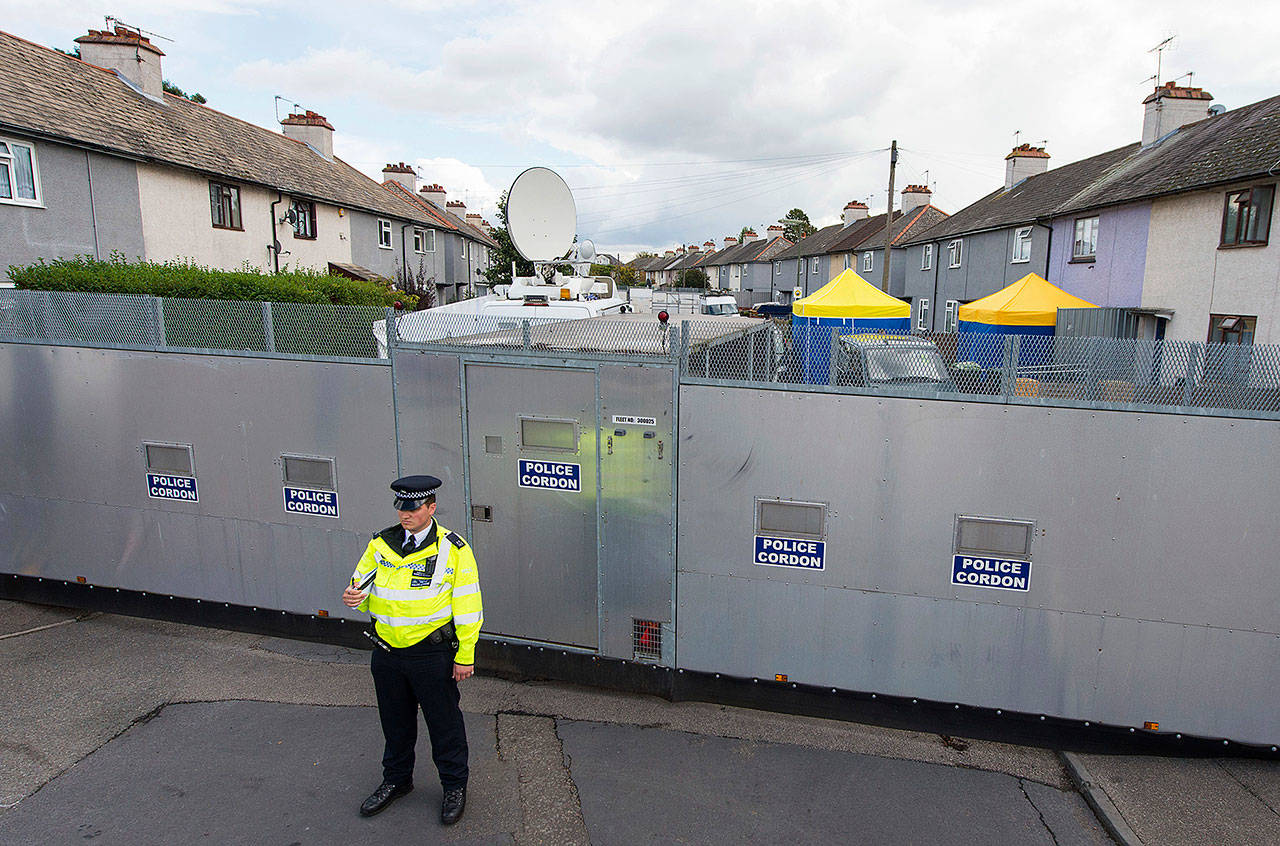 A police officer stands by a cordon on Monday in Sunbury-on-Thames, a London suburb where officials searched the home of a couple who fostered two suspects in last week's subway bombing. (Dominic Lipinski/PA via AP)