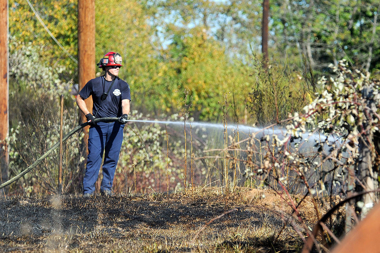 A firefighter sprays water on a few hot spots of a fire that burned in brush along the 900 block of the Ludwig Road on Thursday, Sept. 28, 2017 in Snohomish, Wa. (DougRamsay / For The Herald)