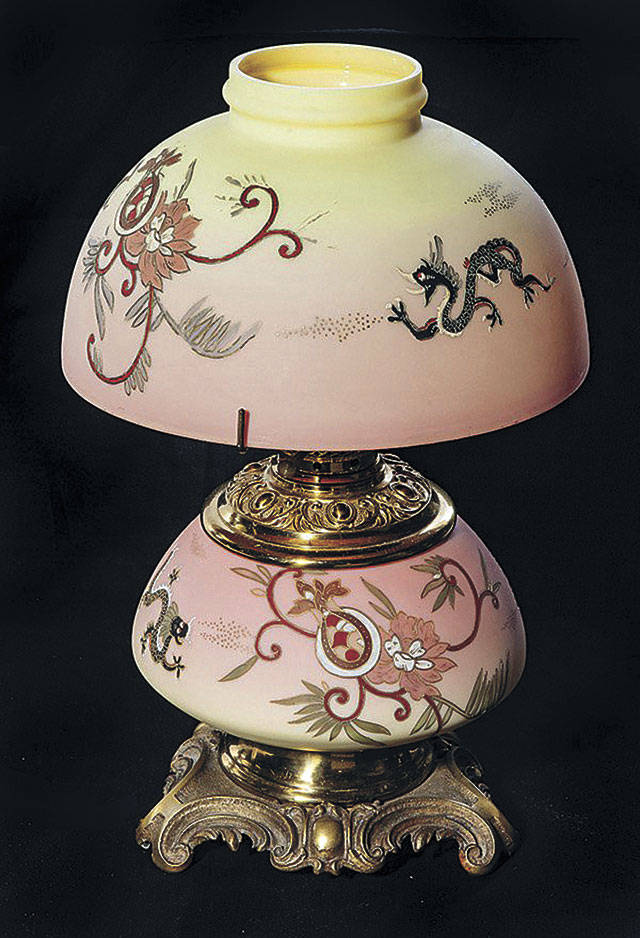 It took $3,335 to buy this student lamp with a font made of Mt. Washington Burmese glass. It is a stylish electrified lamp with an antique base and a shade made later and decorated to match. (Cowles Syndicate Inc.)