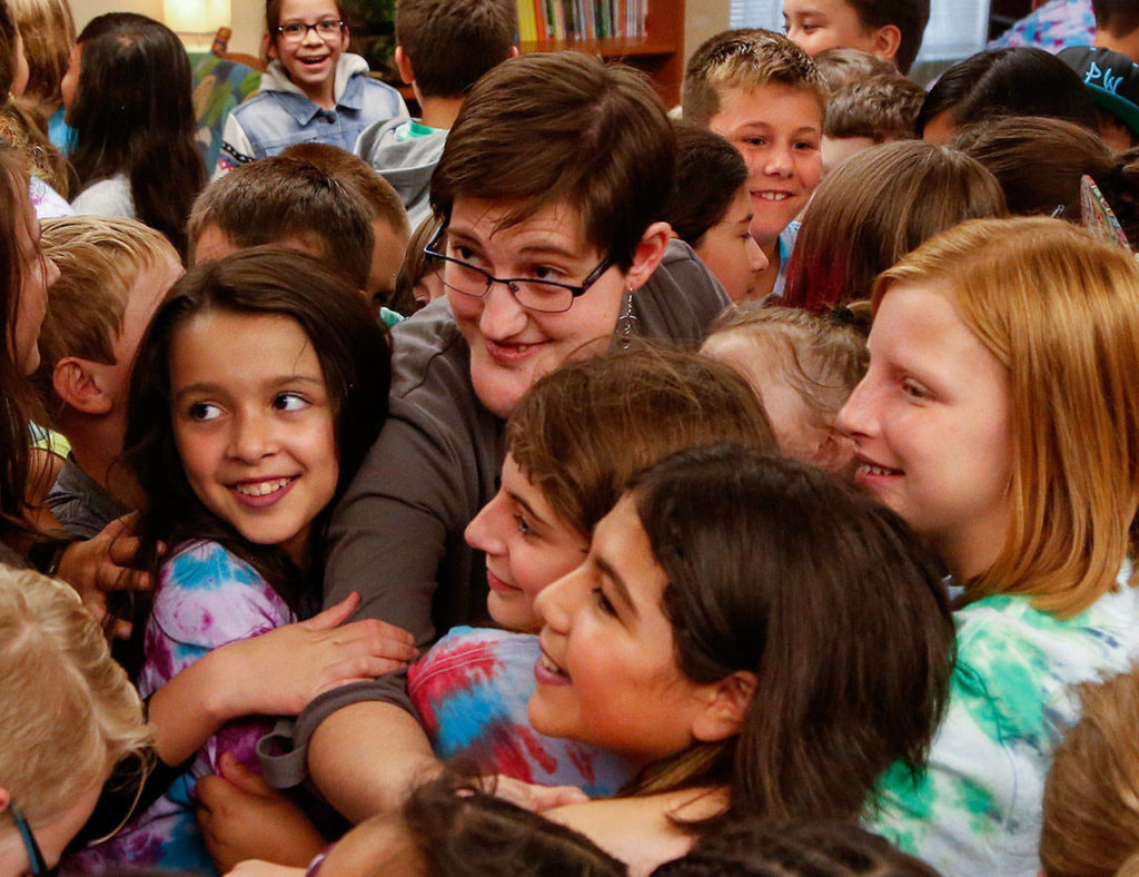 Abby Beauchamp, who was born with a facial abnormality, is surrounded and hugged by the students. (Dan Bates / The Herald)