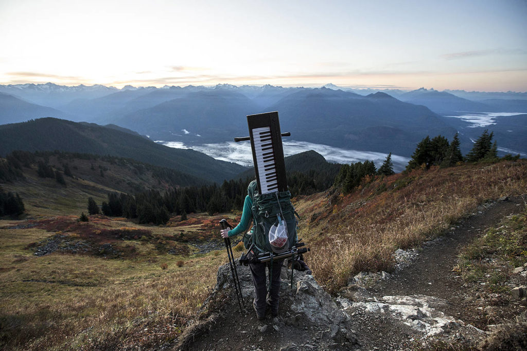 With her Yahama Piaggero keyboard stowed away in her backpack, Rose Freeman stops to take in the view during an early morning ascent of Sauk Mountain on Oct. 5. (Ian Terry / The Herald)