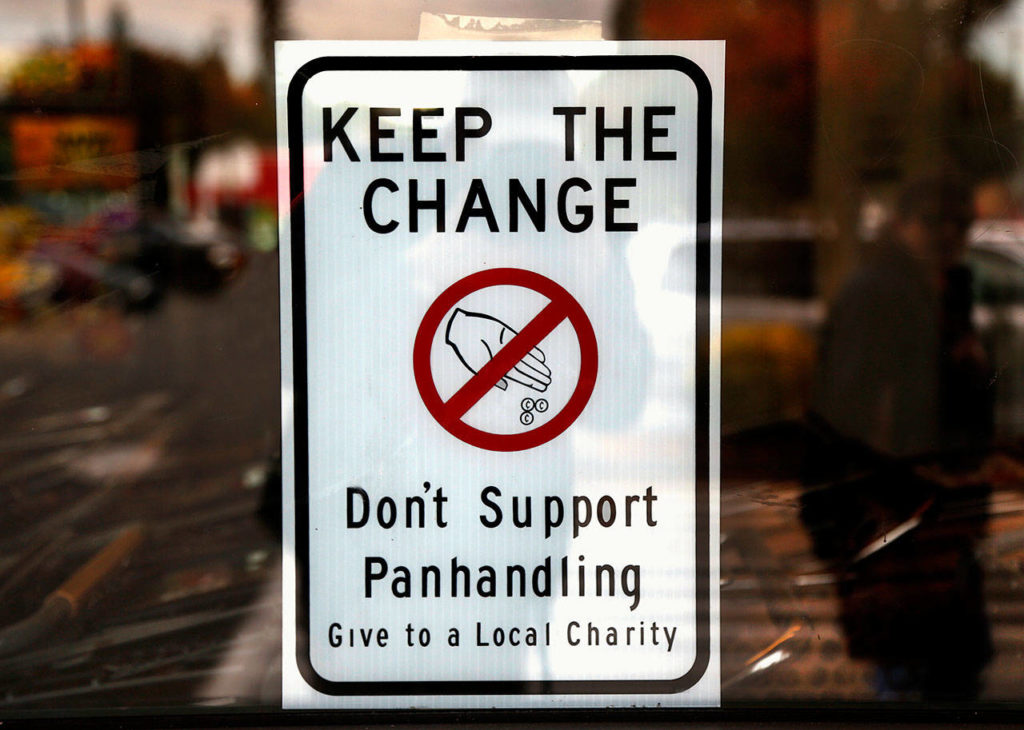 Marysville signage, visible in key locations such as the Safeway parking lot on State Avenue, suggests that people refrain from giving money to panhandlers. (Dan Bates / The Herald)