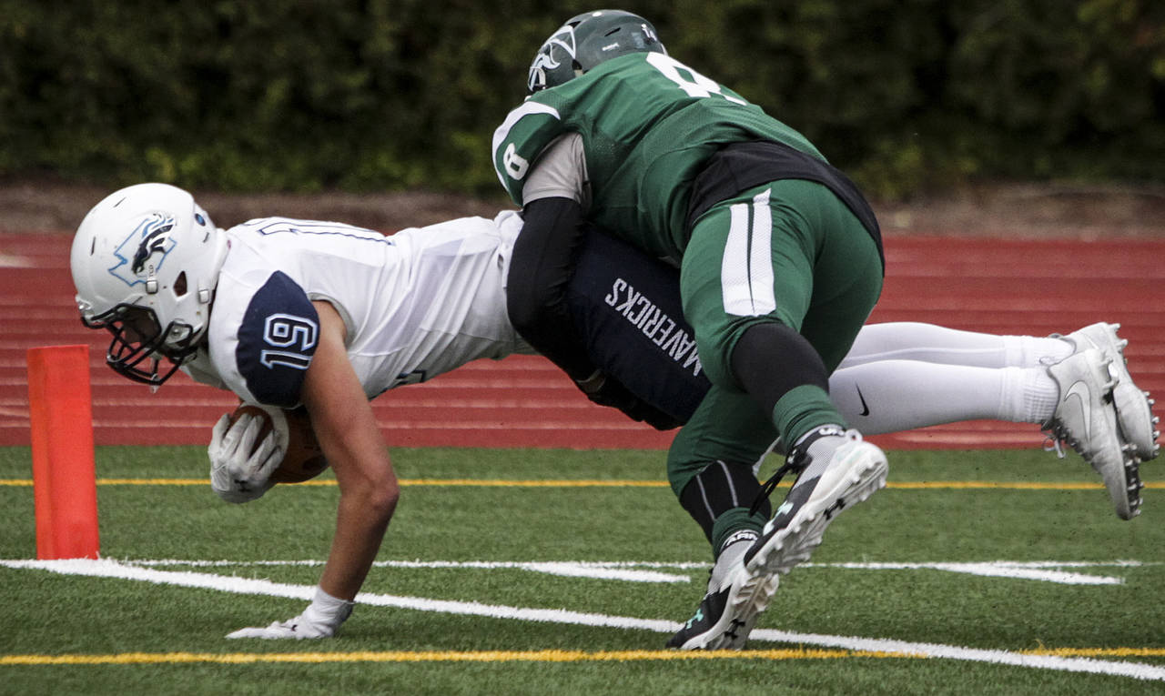 Meadowdale's Will Moloney (left) dives into the end zone for a touchdown as Edmonds-Woodway's Dominic Lawrence defends during a game Oct. 6, 2017, at Edmonds Stadium. (Ian Terry / The Herald)