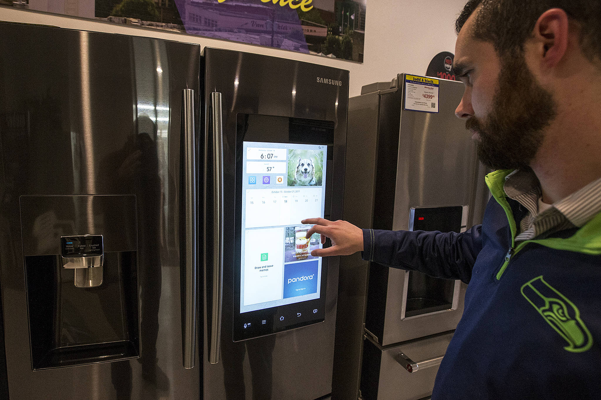 Taylor Long, a sales associate at Judd & Black, flips through the touchscreen on Samsung's Family Hub refrigerator that will be one of the many products on display and sale at the Everett Fall Home Show on Oct. 27, 28 and 29 at Xfinity Arena in Everett. (Ian Terry / The Herald)