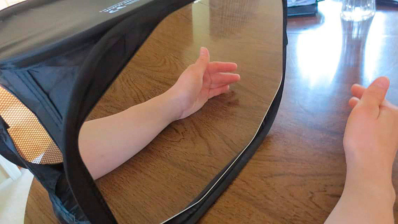 Bardsley does graded motor imagery therapy at home to ease her chronic pain. She puts her affected left arm in a black box with a mirror on it and places her right arm next to it. Then she moves both arms at the same time. When she sees the reflection of her good arm, the hope is that it helps trick her brain into thinking that both arms are pain-free. (Photo courtesy of Jennifer Bardsley)