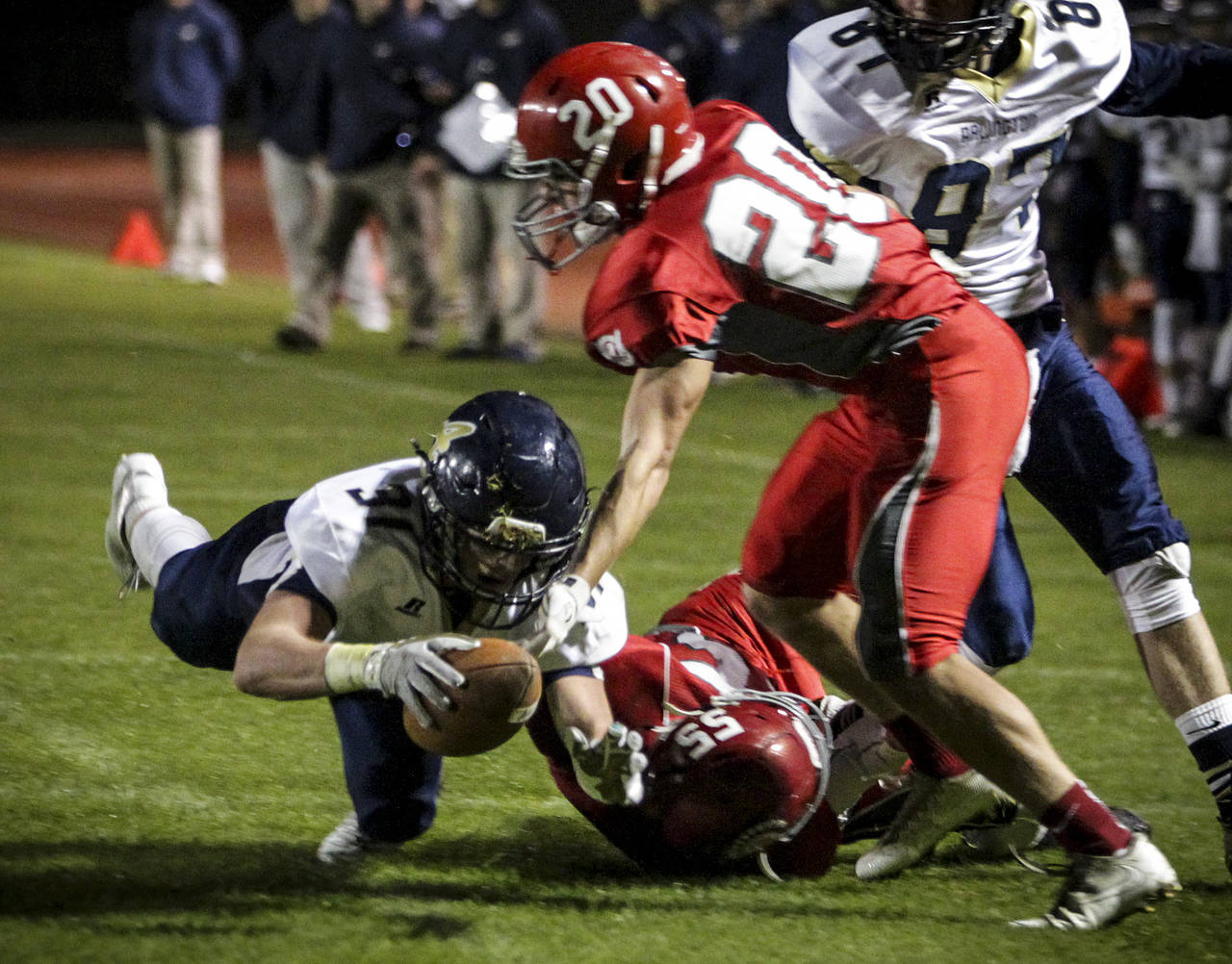 Arlington's Payton Bastien (left) dives forward as Stanwood's Kaiser Hezel defends during the annual Stilly Cup game at Stanwood High School on Oct. 13, 2017. (Ian Terry / The Herald)
