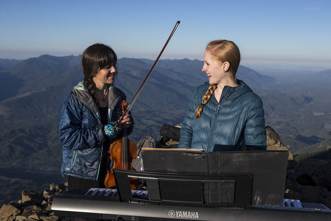 Anastasia Allison (left) and Rose Freeman laugh before playing at sunrise atop Sauk Mountain. (Ian Terry / The Herald)